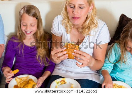 Young family - mother and daughters - is eating hamburger or fast food at home - stock photo