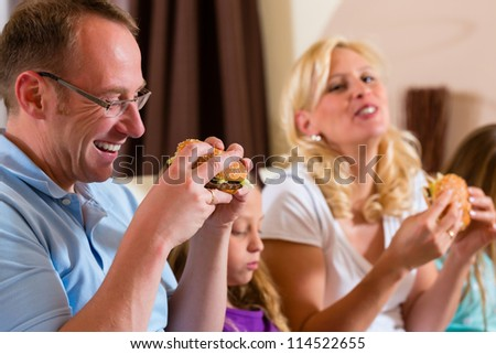 Young family - mother, father and daughters - is eating hamburger or fast food at home - stock photo