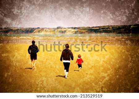 Young family (mother, father and little child) running towards the sea. Back view. Brittany, France. Retro aged photo with scratches.  - stock photo