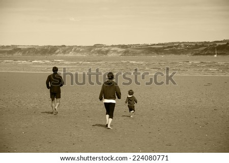 Young family (mother, father and little child) running towards the sea. Back view. Brittany, France. Aged photo. Sepia. - stock photo