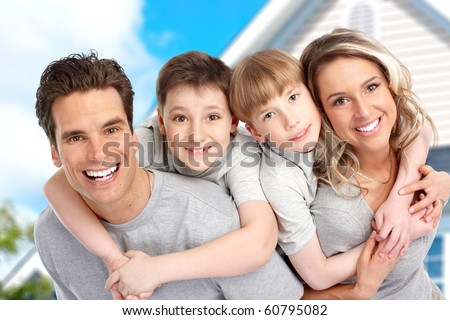 Young family near the new home.  Real estate concept - stock photo