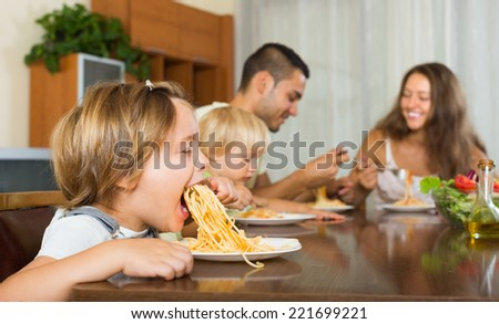 Young family of four eating with spaghetti at table. Focus on girl