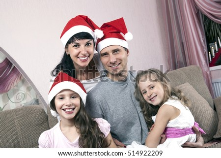 young family of four in Christmas hats