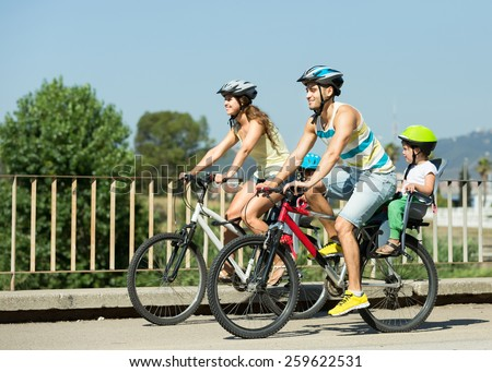 Young family of four people with bikes in sports helmets outdoors - stock photo