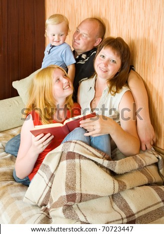 young family of four sitting on couch and reading with the kids - stock photo