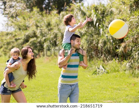 Young family of four spending weekend outdoors - stock photo