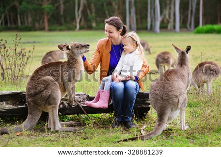 Young family of mother and daughter feeding kangaroo at zoo - stock photo