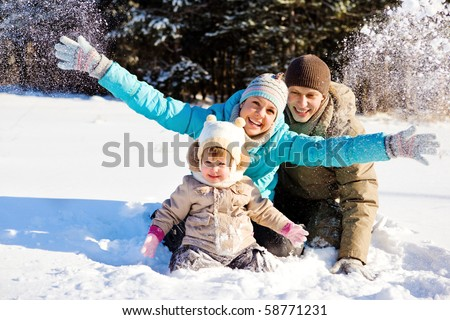 Young family of three throwing snow - stock photo
