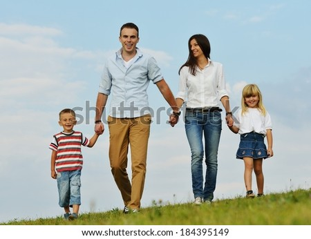 Young family on green summer grass meadow having happy life