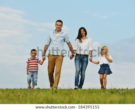 Young family on green summer grass meadow having happy life - stock photo