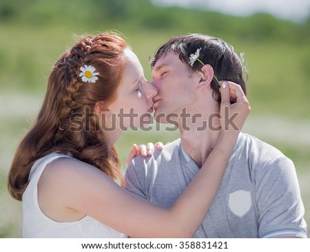 Young family on meadow. Young couple kissing on chamomiles field - stock photo