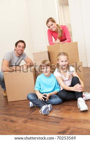 Young family on moving day looking happy among boxes