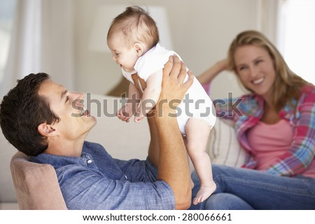 Young Family On Sofa At Home - stock photo