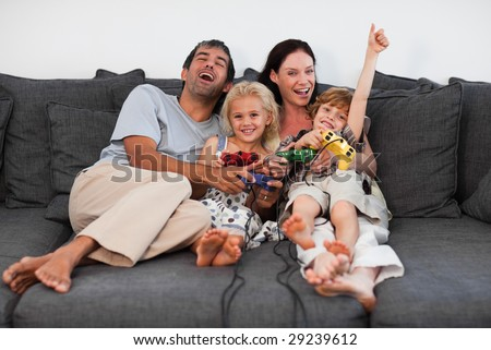 Young Family on Sofa Playing Video games - stock photo