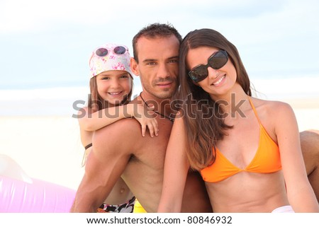 Young family on the beach - stock photo