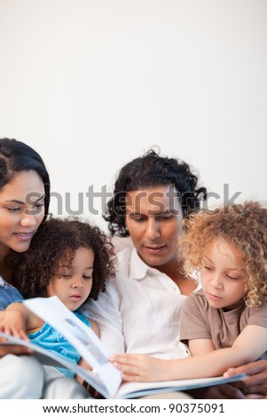 Young family on the couch looking at photo album together