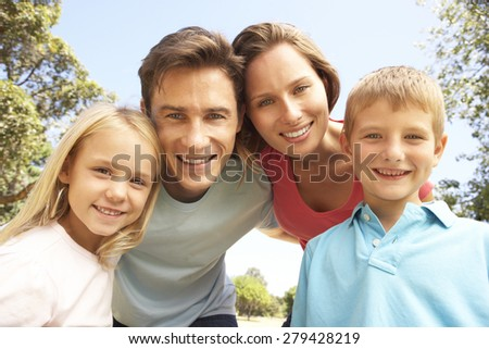 Young Family Outdoors In Park Looking Into Camera
