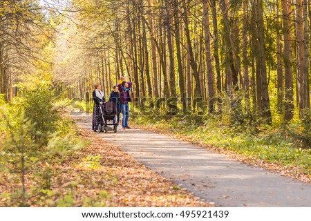 Young Family Outdoors Walking Through Autumn Park