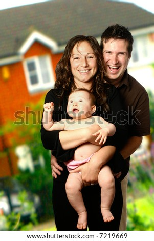 Young family outdoors, with house in background - stock photo