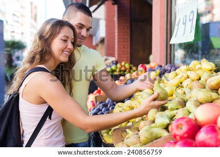 Young family picking fruits out on market and smiling - stock photo