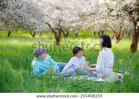Young family picnicking in blooming apple garden on beautiful spring day - stock photo