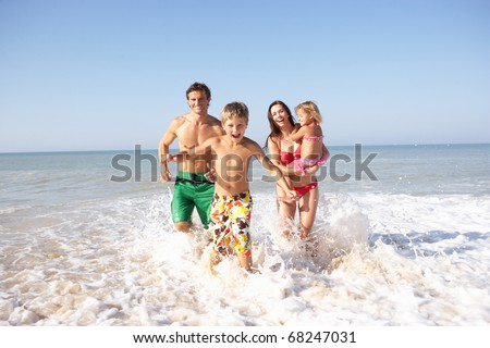 Young family play on beach - stock photo