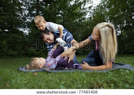 Young family playing at a park - stock photo