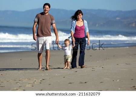 Young family playing at the beach - stock photo