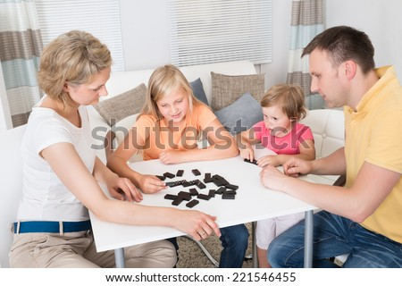 Young Family Playing Domino Game At Home - stock photo