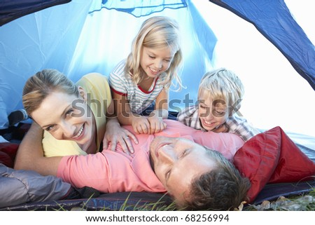 Young family playing in tent - stock photo