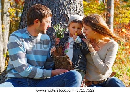 young family playing in the fall forest