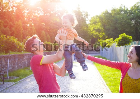Young family playing with a small child on the walk in the Park. - stock photo