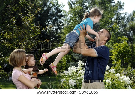 Young family plays on in the backyard. - stock photo