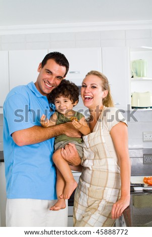 young family portrait in modern kitchen