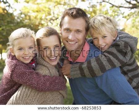 Young family pose in park - stock photo