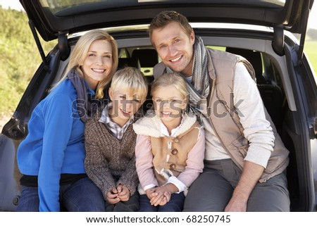 Young family pose together at rear of car - stock photo