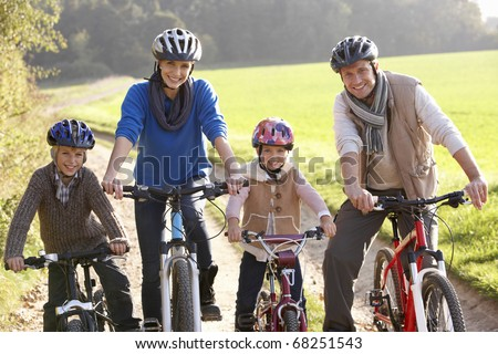 Young family pose with  bikes in park - stock photo