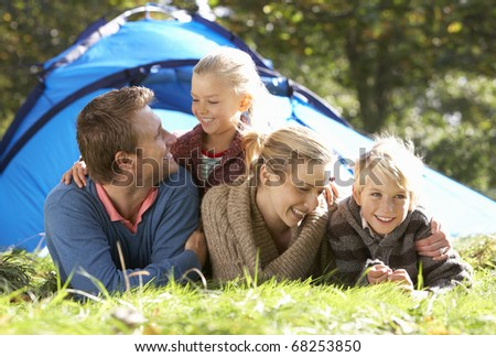 Young family poses outside of tent - stock photo