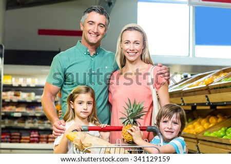 Young Family posing together with trolley at supermarket - stock photo