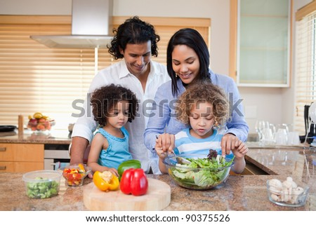 Young family preparing salad together in the kitchen