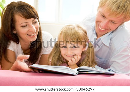 Young family reading a book - stock photo