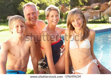 Young Family Relaxing By Pool In Garden - stock photo