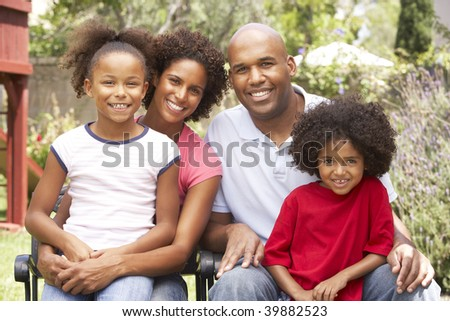 Young Family Relaxing In Garden Together - stock photo