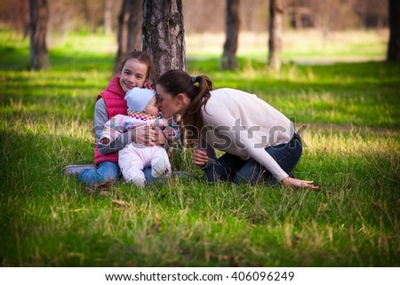 Young family relaxing in park on the grass