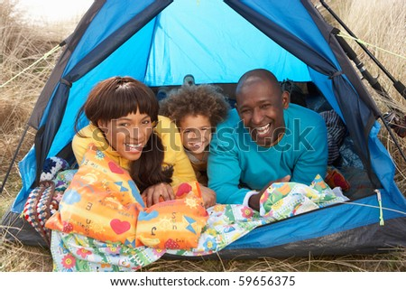 Young Family Relaxing Inside Tent On Camping Holiday - stock photo