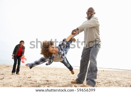 Young Family Relaxing On Beach Camping Holiday - stock photo