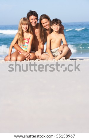Young Family Relaxing On Beach Holiday