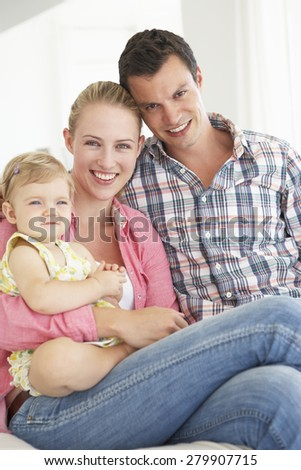 YOung Family Relaxing On Sofa
