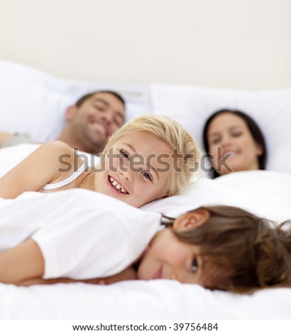 Young family relaxing together in parent's bed
