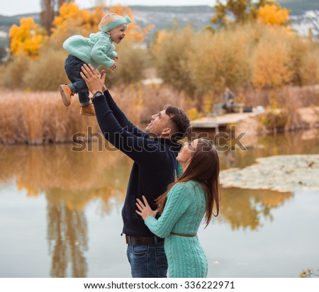 Young family resting on the lake shore - stock photo